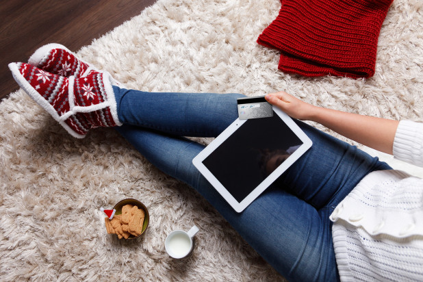 Girl sitting on floor with Christmas cookies and shopping online on tablet – Popular Black Friday and Cyber Monday Products Sold by Online Businesses