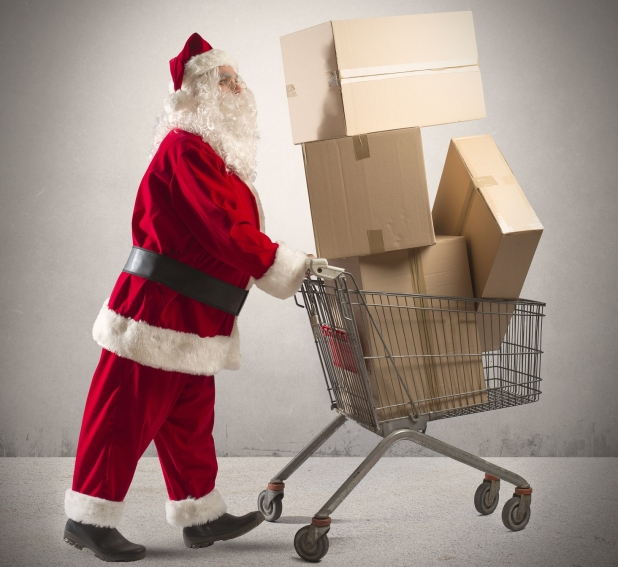 Santa pushing a shopping cart filled with boxes for return shipping.