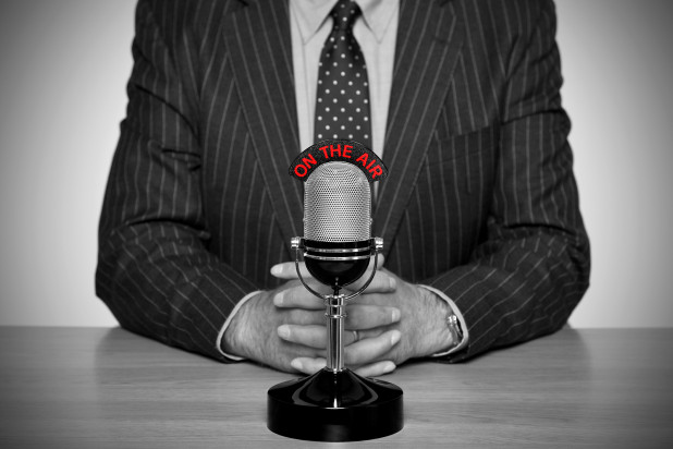 Man in suit in front of microphone – representing Endicia's podcast interview with Mixergy