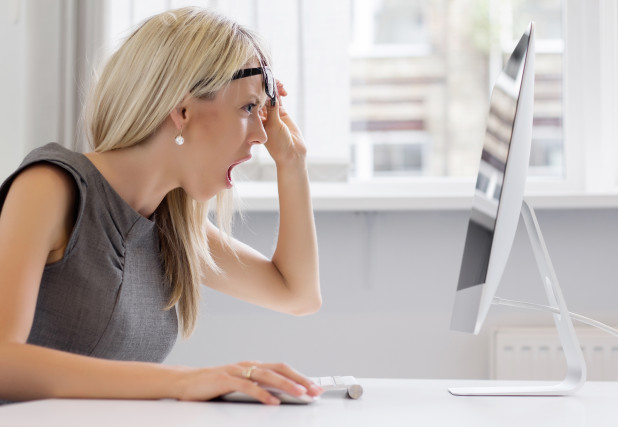 Woman shocked looking at computer screen – representing top online shopping pet peeves that online businesses should avoid based on ShippingEasy whitepaper
