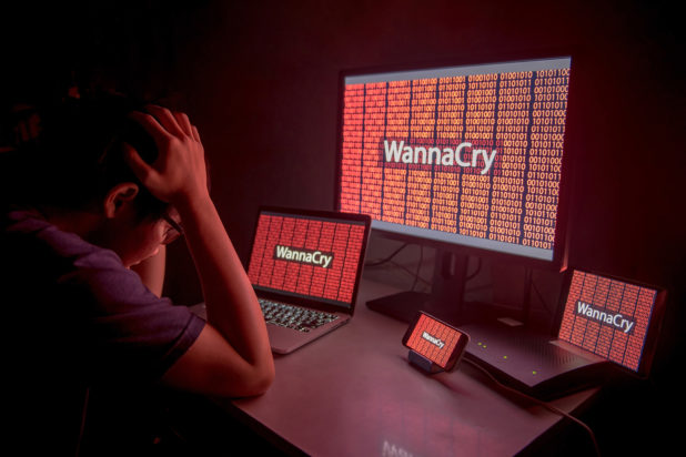 Upset man in front of screens depicting WannaCry ransomware